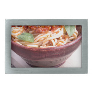 Cooked spaghetti in a brown small wooden bowl rectangular belt buckles
