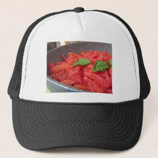 Cooking homemade tomato sauce using fresh summer t trucker hat