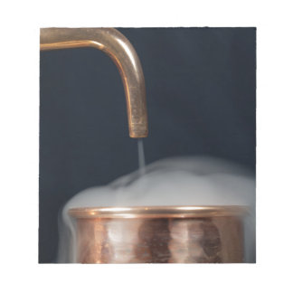 copper pipe of a distillery with steam. notepad