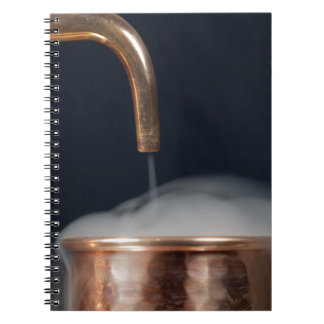 copper pipe of a distillery with steam. spiral notebook