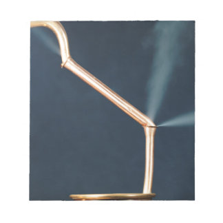 Copper pipes with a leak and steam. notepad