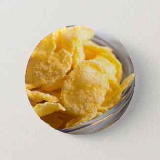 Cornflakes in a transparent bowl closeup 2 inch round button