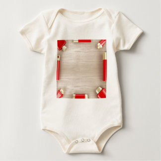 Cosmetic products on wooden table baby bodysuit