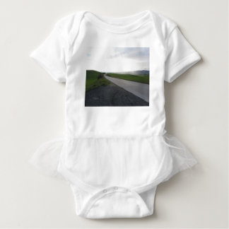 Country road over rolling green hills and valleys baby bodysuit