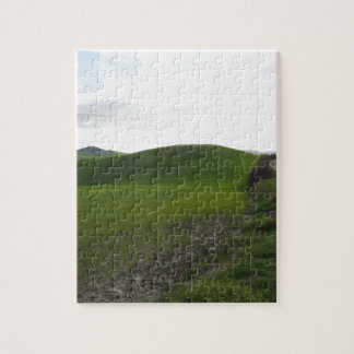 Country road over rolling green hills and valleys jigsaw puzzle