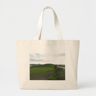 Country road over rolling green hills and valleys large tote bag