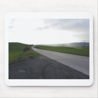 Country road over rolling green hills and valleys mouse pad