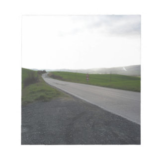 Country road over rolling green hills and valleys notepad