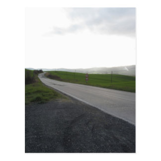 Country road over rolling green hills and valleys postcard