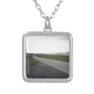 Country road over rolling green hills and valleys silver plated necklace