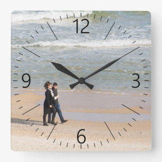 Couple walking along a shoreline wall clock