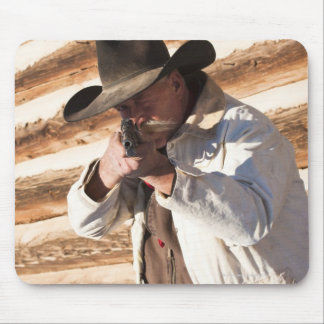 Cowboy aiming his gun, standing by an old log mouse pad