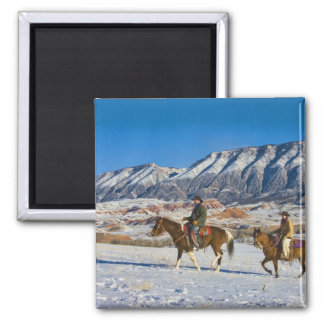 Cowboy and Cowgirl riding Horse through the Snow Square Magnet