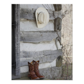 Cowboy boots and hat outside of log cabin poster