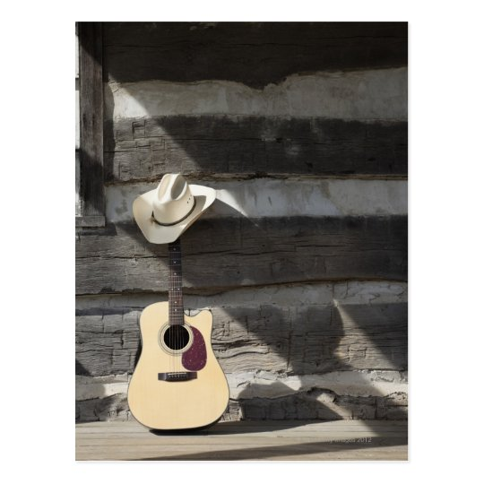 Cowboy hat on guitar leaning on log cabin postcard