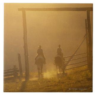 Cowboys riding through gate at dusk tile