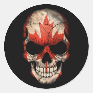 Crâne canadien de drapeau sur le noir autocollant rond