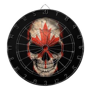 Crâne canadien de drapeau sur le noir jeu de fléchettes