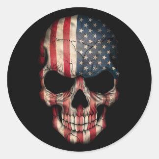 Crâne de drapeau américain sur le noir adhésif rond