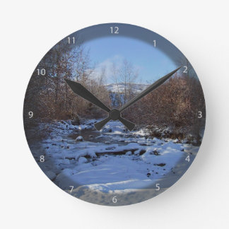 Creek covered by ice round clock