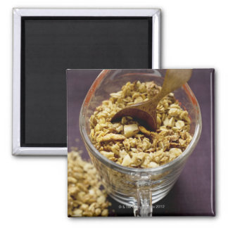Crunchy muesli with wooden spoon in a measuring square magnet