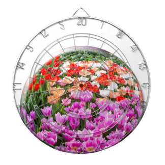 Crystal ball with various colored tulips on white dartboard with darts