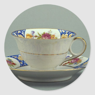 Cup and saucer with colorful flower designs on it. round sticker