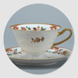 Cup and saucer with colorful flowers on it. round sticker