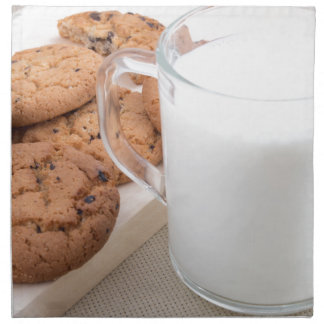 Cup with milk and oatmeal cookies napkin