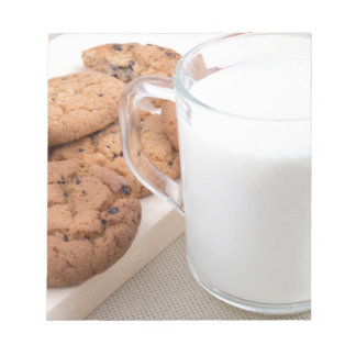 Cup with milk and oatmeal cookies notepad