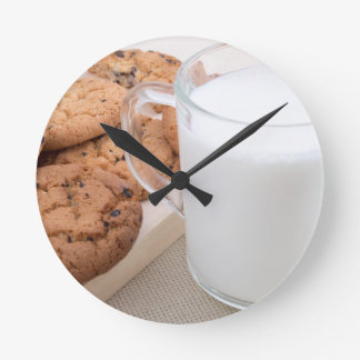 Cup with milk and oatmeal cookies round clock
