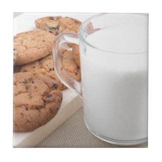 Cup with milk and oatmeal cookies tile