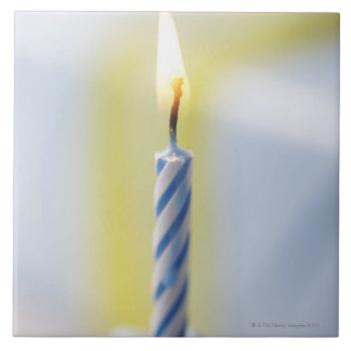 Cupcake with candle, close-up (focus on flame) ceramic tile