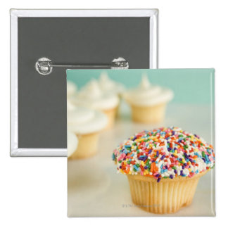 Cupcakes, focus on one in front with 2 inch square button