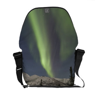 Curtains of aurora borealis dance across the sky messenger bags