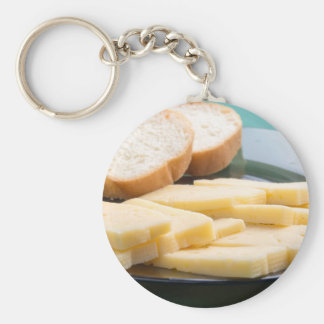 Cut slices of cheese on a plate close-up basic round button keychain