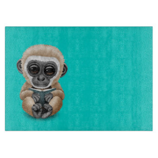 Cute Baby Gibbon Reading a Book on Blue Cutting Board
