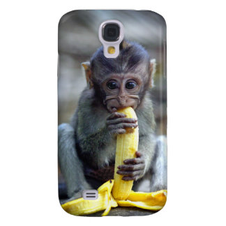 Cute baby macaque monkey eating banana