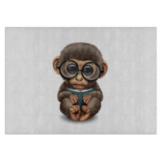 Cute Baby Monkey Reading a Book on White Cutting Board