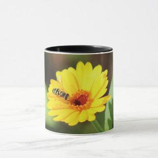cute bee collecting nectar on a beautiful flower mug