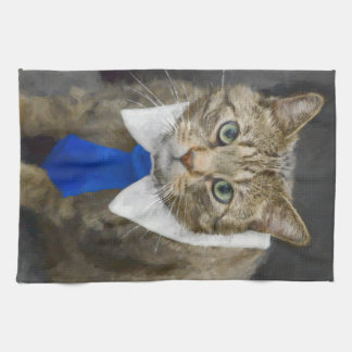Cute green-eyed brown tabby cat wearing a blue tie kitchen towel