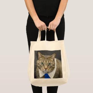 Cute green-eyed brown tabby cat wearing a blue tie tote bag