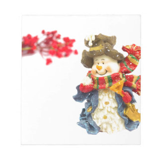 Cute snowman figurine with red berries on white notepad