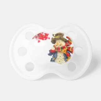 Cute snowman figurine with red berries on white pacifier