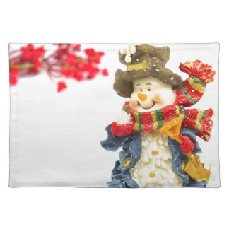 Cute snowman figurine with red berries on white placemat