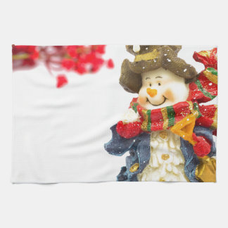 Cute snowman figurine with red berries on white towel