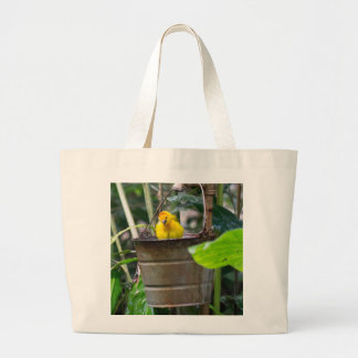 Cute, yellow bird bathing in a bucket large tote bag
