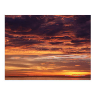 Dark clouds in orange streaked sky postcard