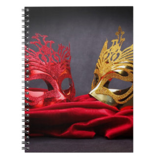 Decorated masquerade mask on red velvet note books
