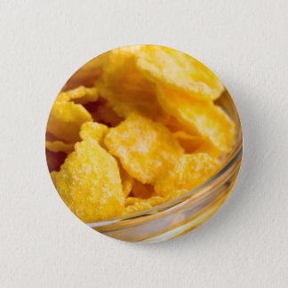 Defocused and blurred image of dry corn flakes 2 inch round button